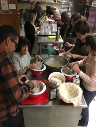 A cooking class at the Stroum JCC in Seattle made an entire meal. People in the front are grating potatoes for dumplings, while those in the back are preparing mushrooms, cabbage slaw, and making chocolate hazelnut cookies.